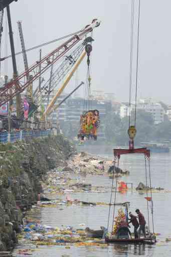 Crane workers immerse idols in the Hussain Sagar Lake (Credit: AFP)