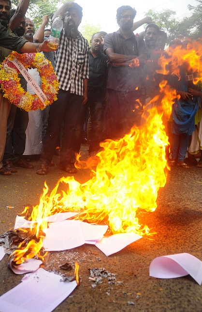 Kamalsy and his supporters burn copies of his 'Smashanangalude Note Pusthakam'. Photo: TA Ameerudheen