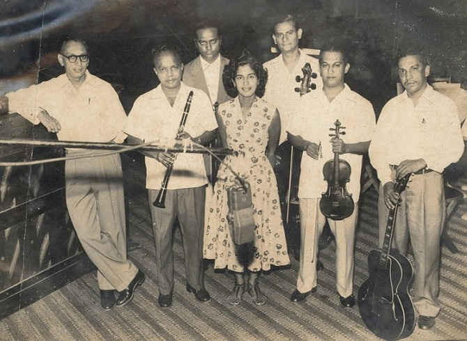 Anthony Gonsalves (back row, left) in a recording studio with other musicians, including the pianist Lucila Pacheco.