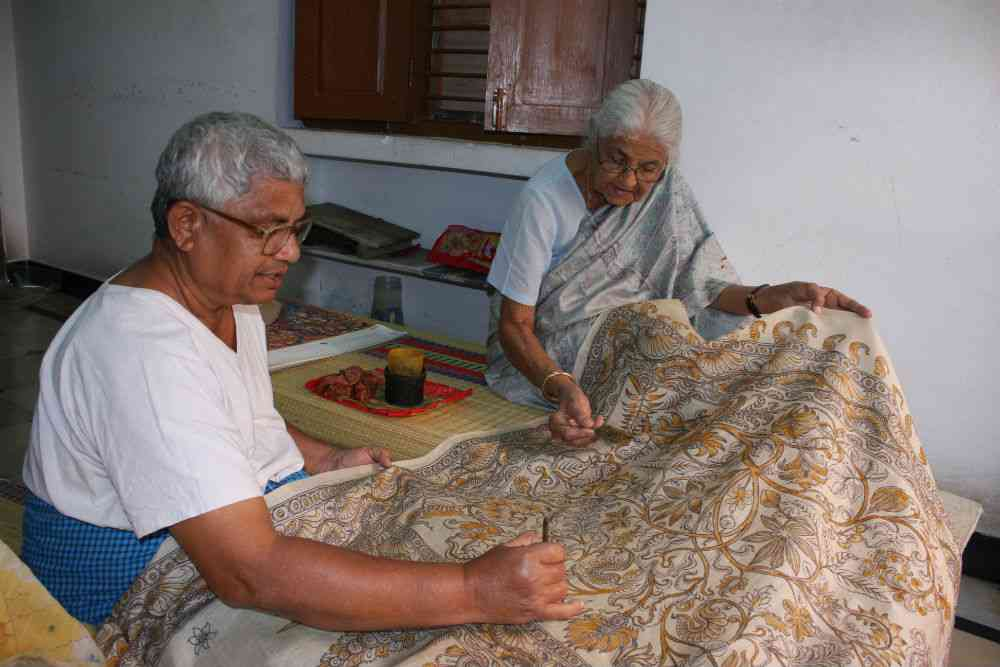 Kalesham, a weaver, touches up a wall hanging while Suraiya Hasan Bose adds a detail.