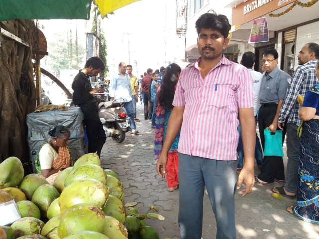 Mohammed Aziz at his coconut stall, right outside a bank with a long queue.