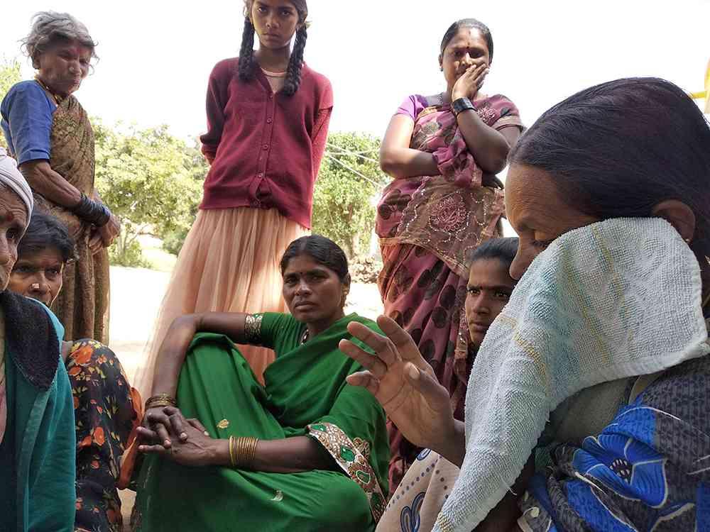 Village women gather around Nandish's mother at their home.