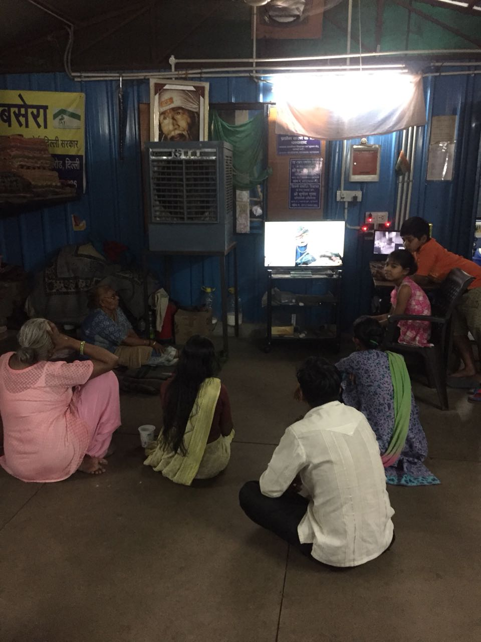 While the air cooler may not work, the TV does, as the women watch a serial at a night shelter in Lodi Road, New Delhi. Photo Credit: Anasuya Basu