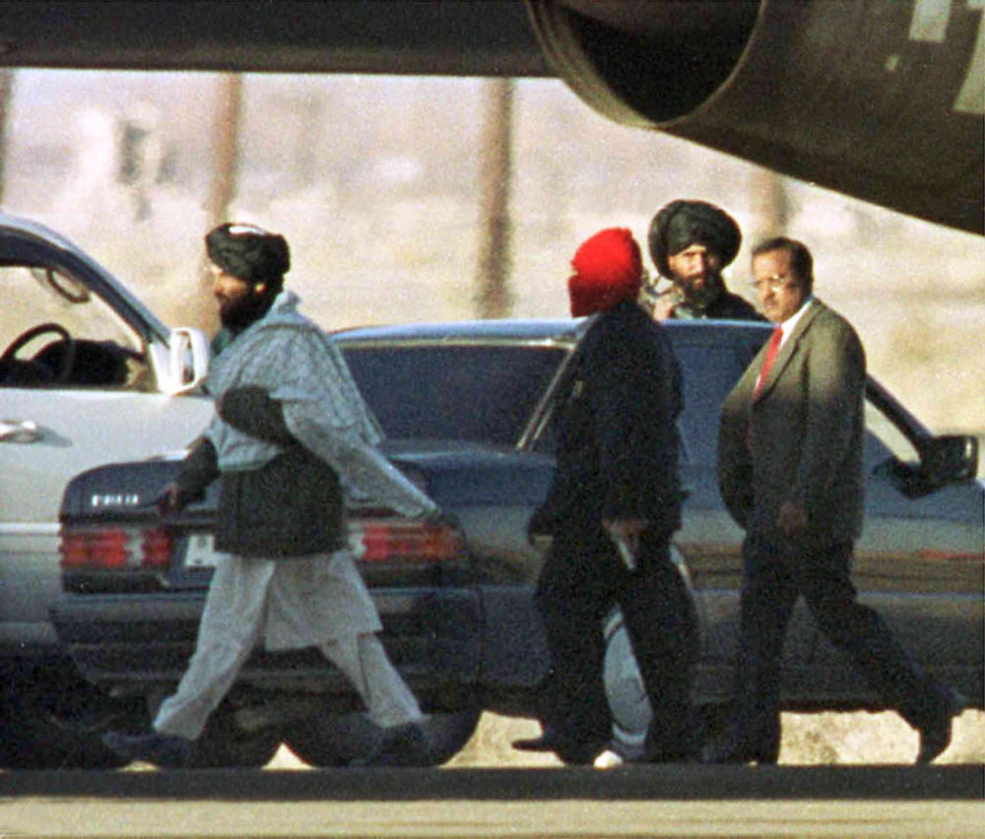 A masked hijacker carrying a pistol walks with a member of the Afghan Taliban (left) and Ajit Doval (right), then India's Intelligence Bureau chief, in Kandahar airport, in Afghanistan, on December 31, 1999.