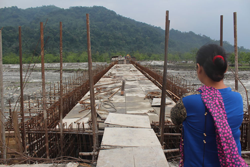 A Idu lady looks at the unfinished Dipu Nallah bridge, with Tezu on the other side. Photo credit: Mirza Zulfiqur Rahman