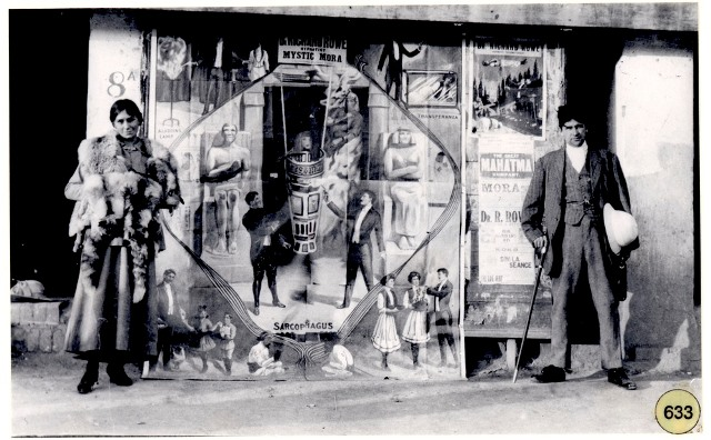 Mystic Mora and Doc Rowe standing in front of posters advertising their performance at the Garrison Theatre, Peshawar (1917).
