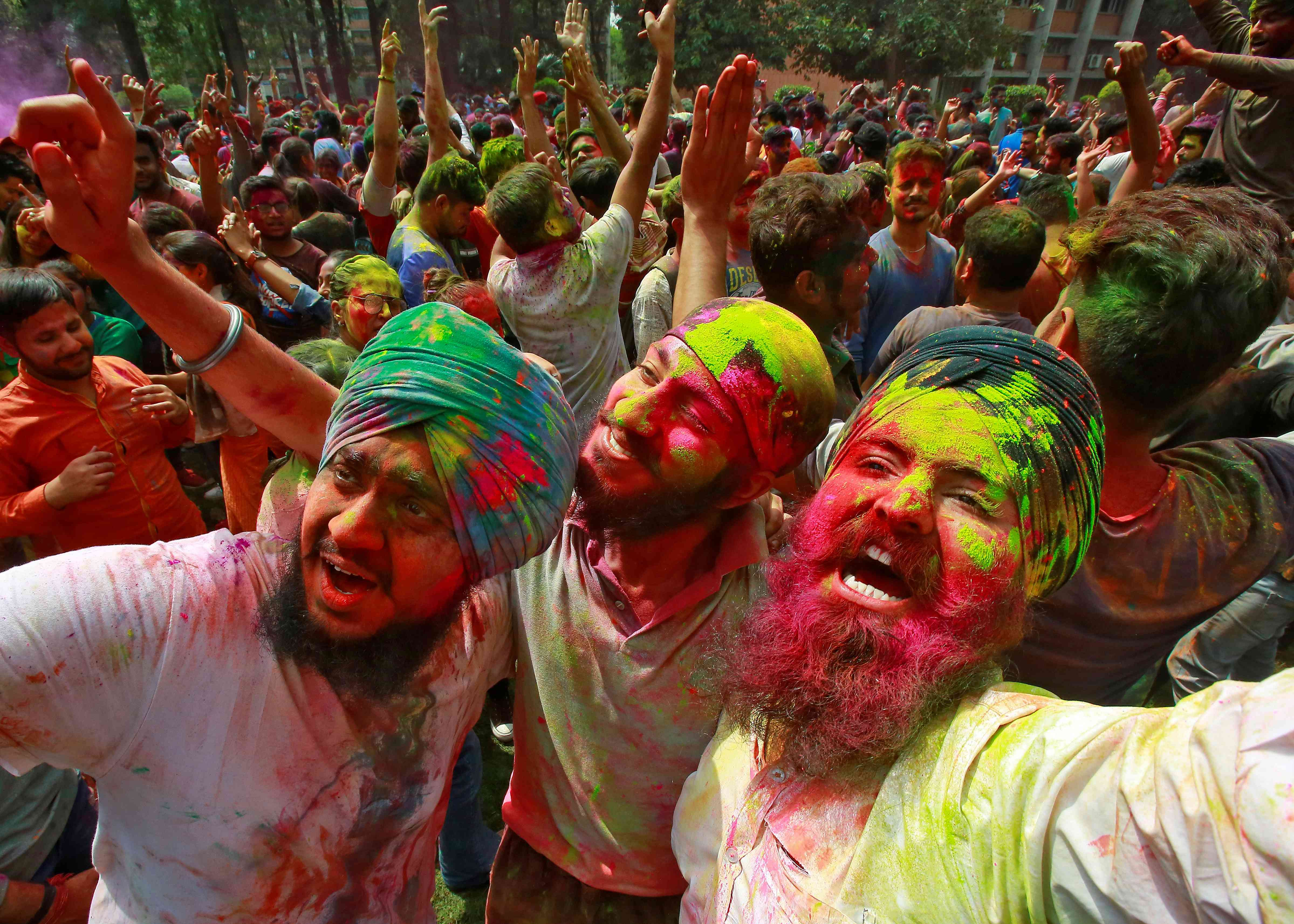Students with their faces smeared in colours dance as they celebrate Holi on a university campus in Chandigarh. | Credit: Reuters