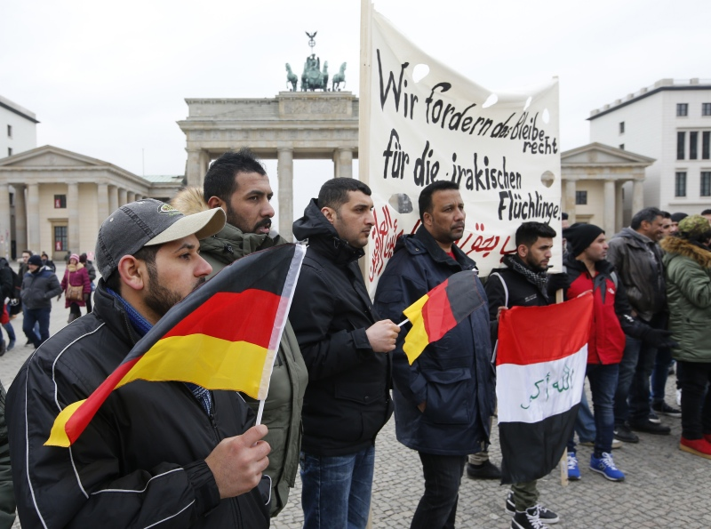 People protest against the deportation of Iraqi refugees from Germany at the Brandenburg Gate in Berlin, in February. The banner should read: We are demanding right to stay for Iraqi refugees. Photo credit: Fabrizio Bensch/Reuters.