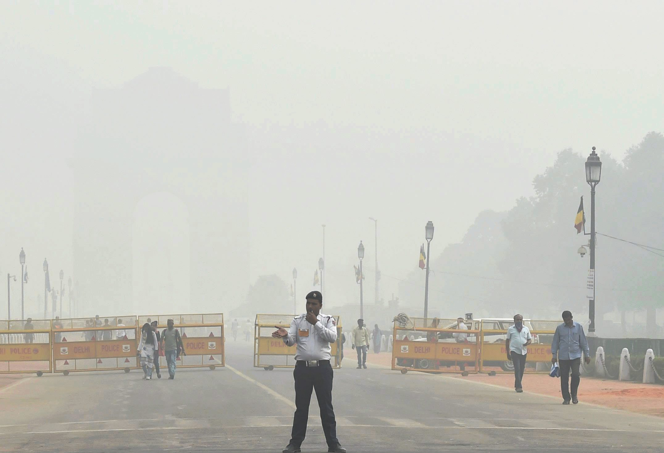 A traffic policeman on duty near India Gate, which was enveloped in a thick cloud of smog, on Tuesday (PTI)