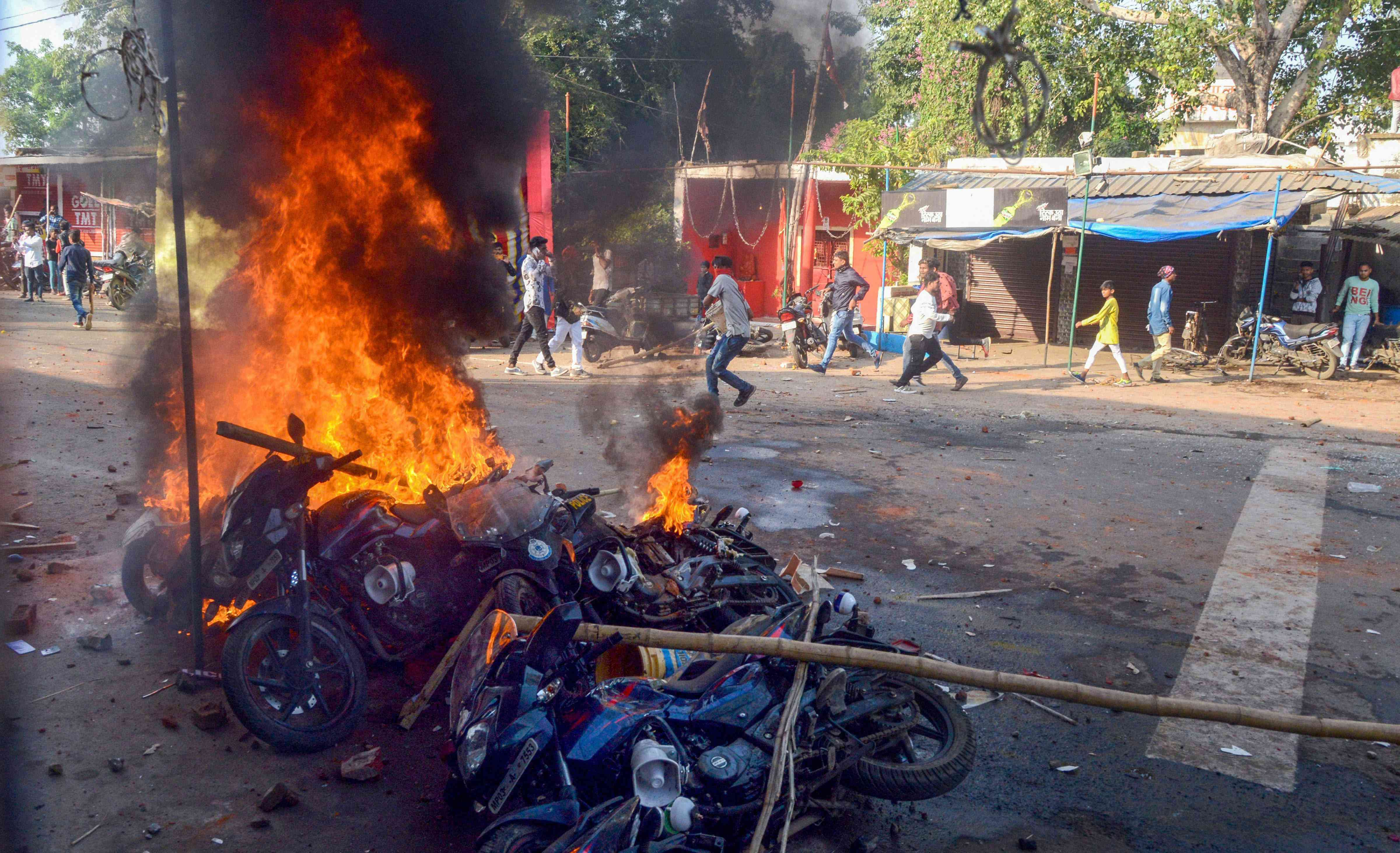 Protestors set motorcycles ablaze during a clash with police personnel over a ban on idol immersion in the Narmada (Photo credit: PTI)