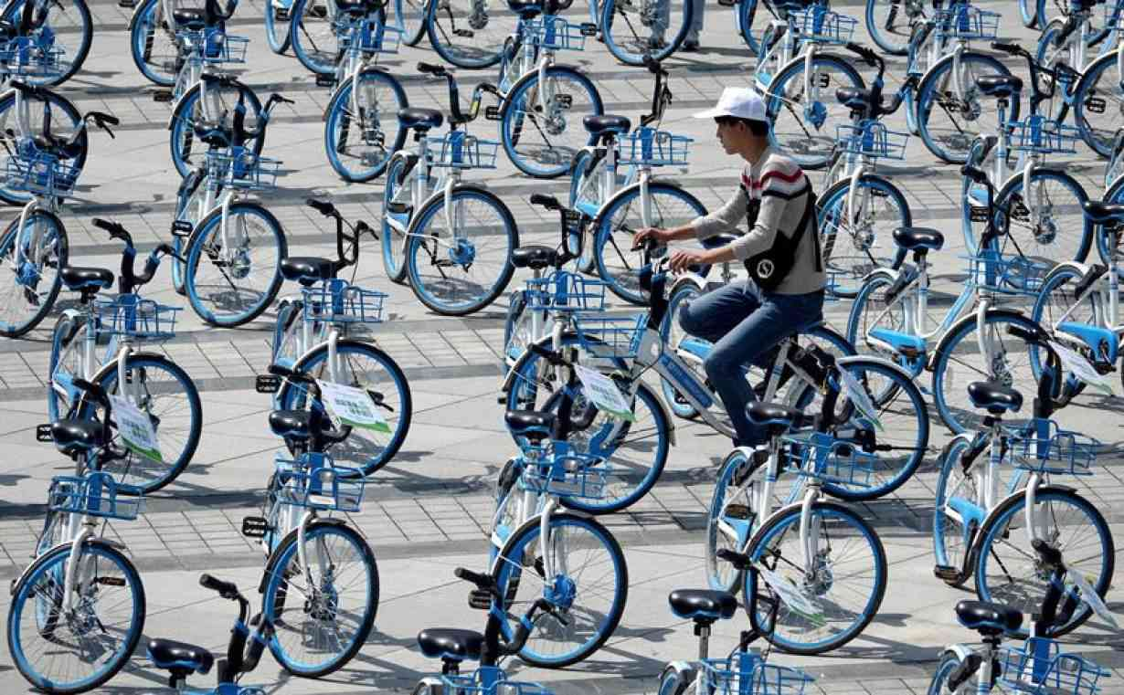 A man rides a bicycle of bike-sharing firm Hellobike amid Hellobike bicycles placed on a plaza a day ahead of the World Car Free Day, in Zhengzhou, Henan province, China September 21, 2018. Photo credit: Stringer/Reuters