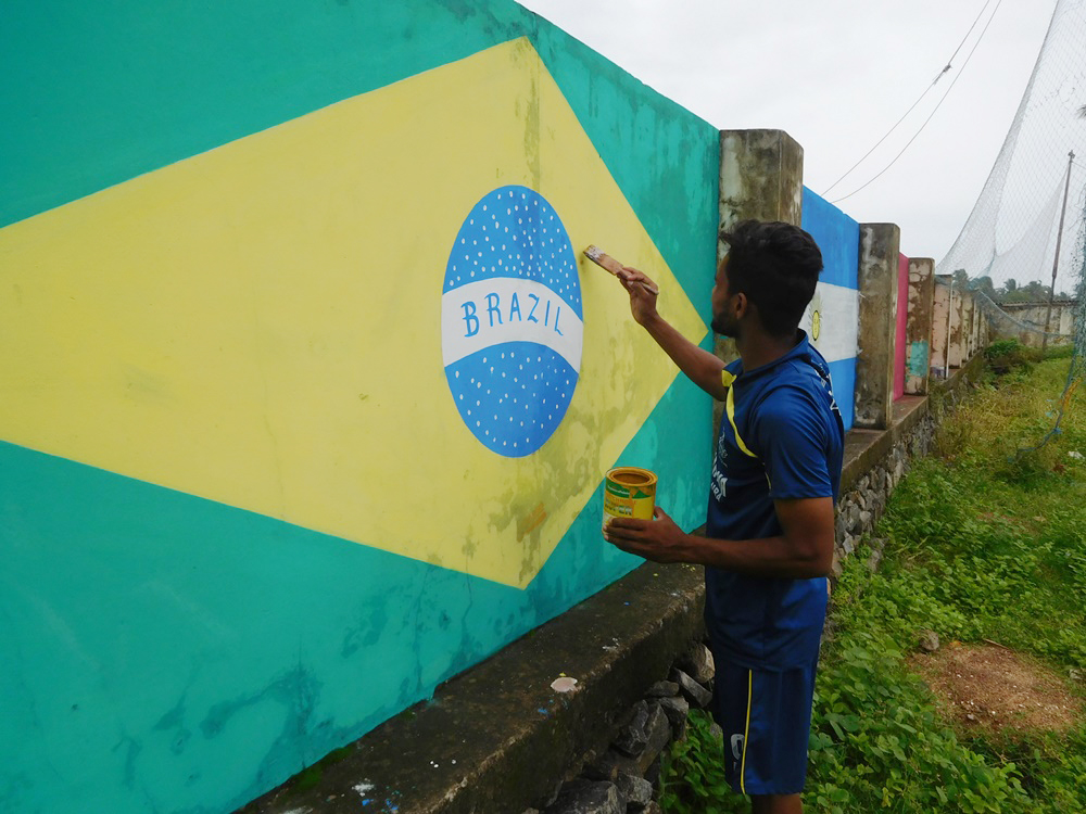 A Brazilian football fan paints a wall in Ninan Valappu in Kozhikode. (Photo credit: TA Ameerudheen).