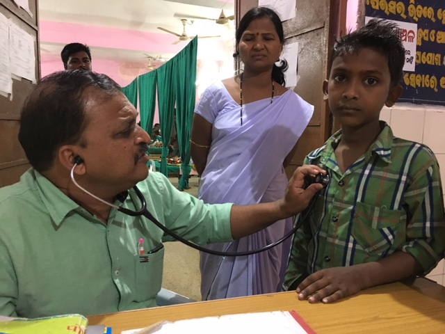 Dr Santosh Mishra examining a child at Malkangiri's district headquarters hospital. Photo: Priyanka Vora.