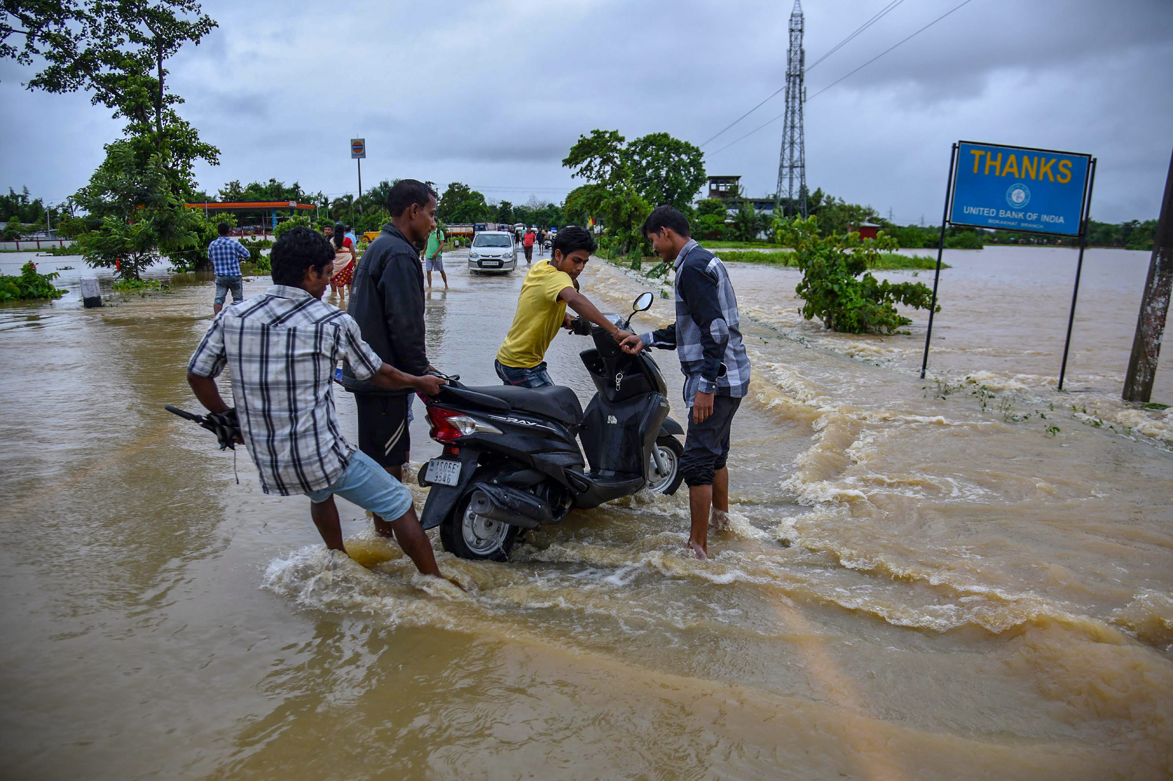 People wade through the flooded NH 27 after rains in Bokakhat sub-division of Golaghat district in Assam. Photo credit: PTI