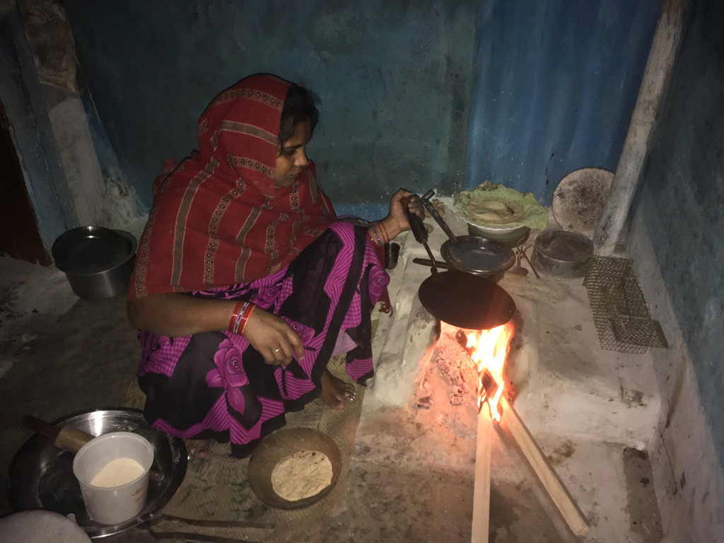 An Andhera Gher resident using wood blocks to fuel her earthen stove to cook dinner. Photo credit: Menaka Rao.