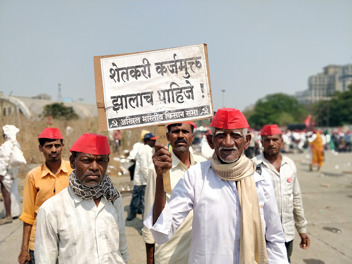 "The protest is spearheaded by Akhil Bharatiya Kisan Sabha. A protestor holds up a sign that reads, ""Farmers ought to be free from debt""."