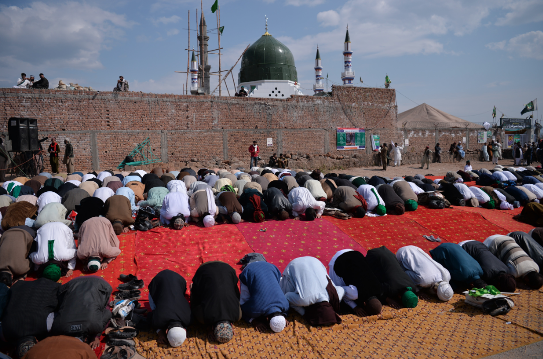 Pakistanis offer noon prayers at the tomb of Mumtaz Qadri in the outskirts of Islamabad. (Credit: Aamir Qureshi / AFP)