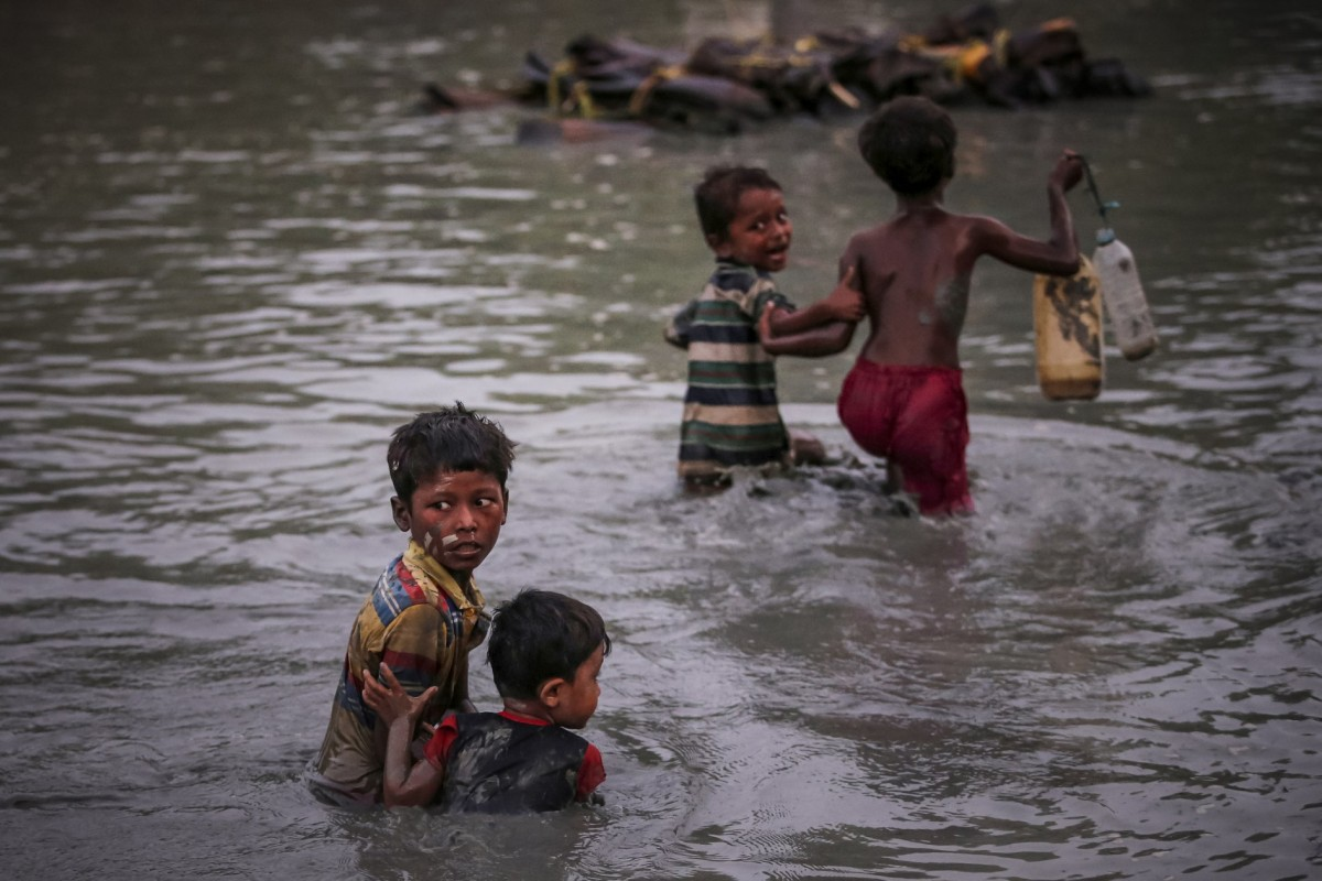 Rohingya siblings cross the Naf River along the Bangladesh-Myanmar border in Palong Khali, near Cox's Bazar, Bangladesh, on November 1, 2017. Photo: Adnan Abidi/Reuters