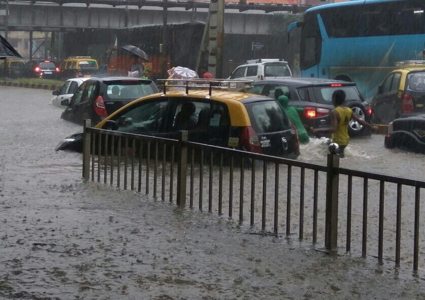 Vehicles struggle to make their way through a deluged road on Tuesday. Credit: IANS