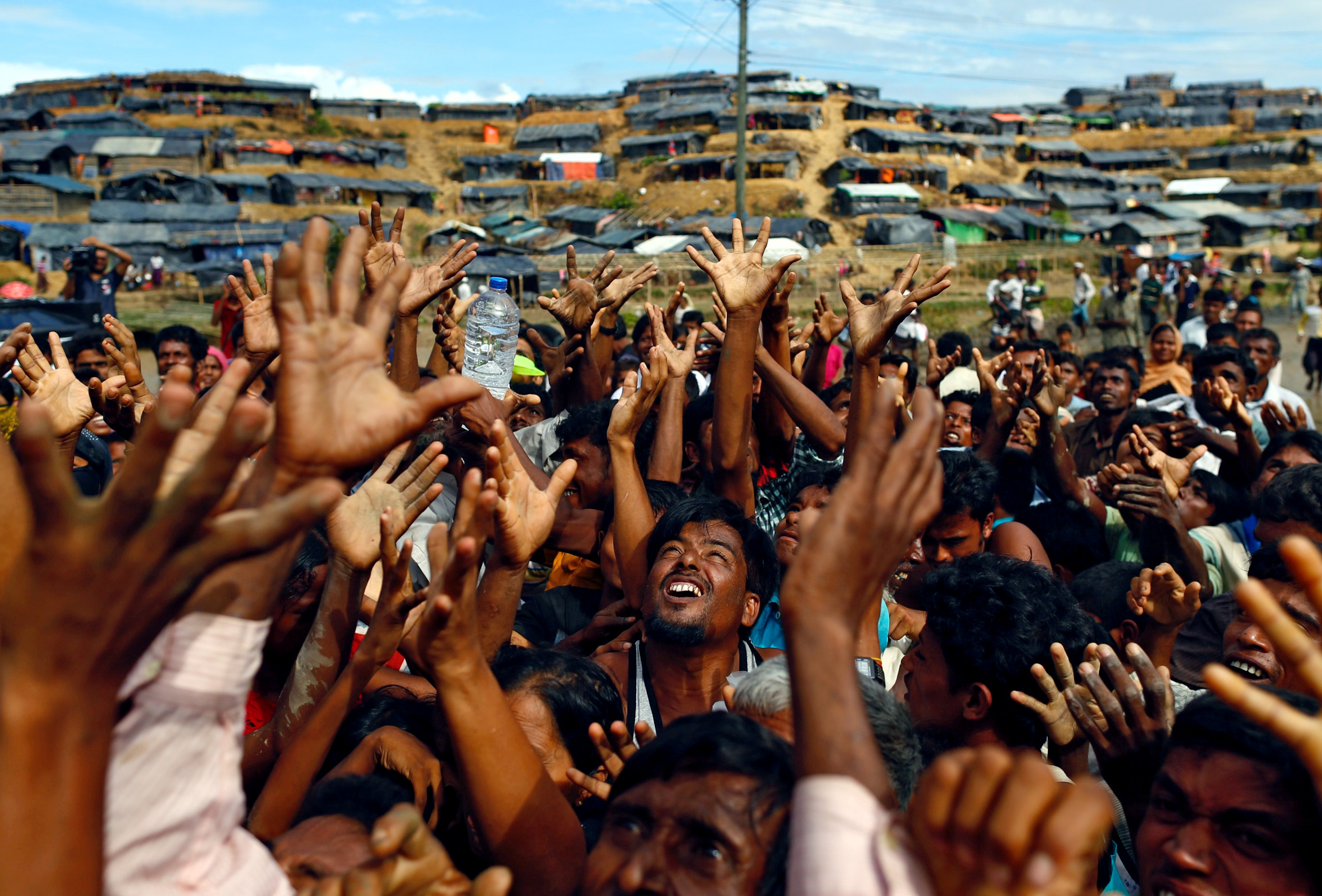 Rohingya refugees stretch their hands to receive aid at a camp in Cox's Bazar in Bangladesh. (Credit: Danish Siddiqui / Reuters)