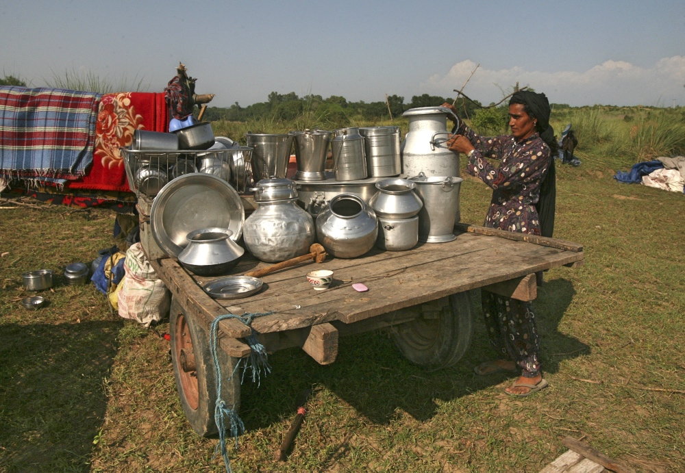 A woman, who fled her home after heavy shelling between India and Pakistan along the Jammu and Kashmir border in 2014, arranges her utensils at a relief camp. (Photo credit: Mukesh Gupta/Reuters).