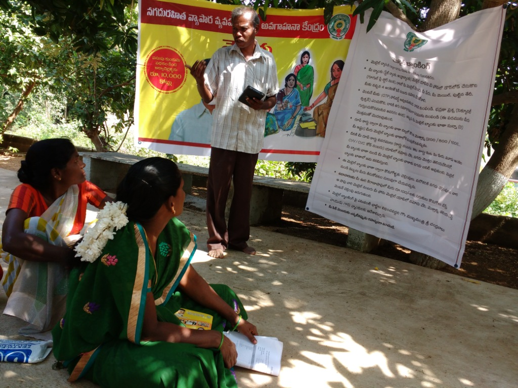 K Mohan explains the benefits of mobile banking to members of a self-help group in Annoor village.