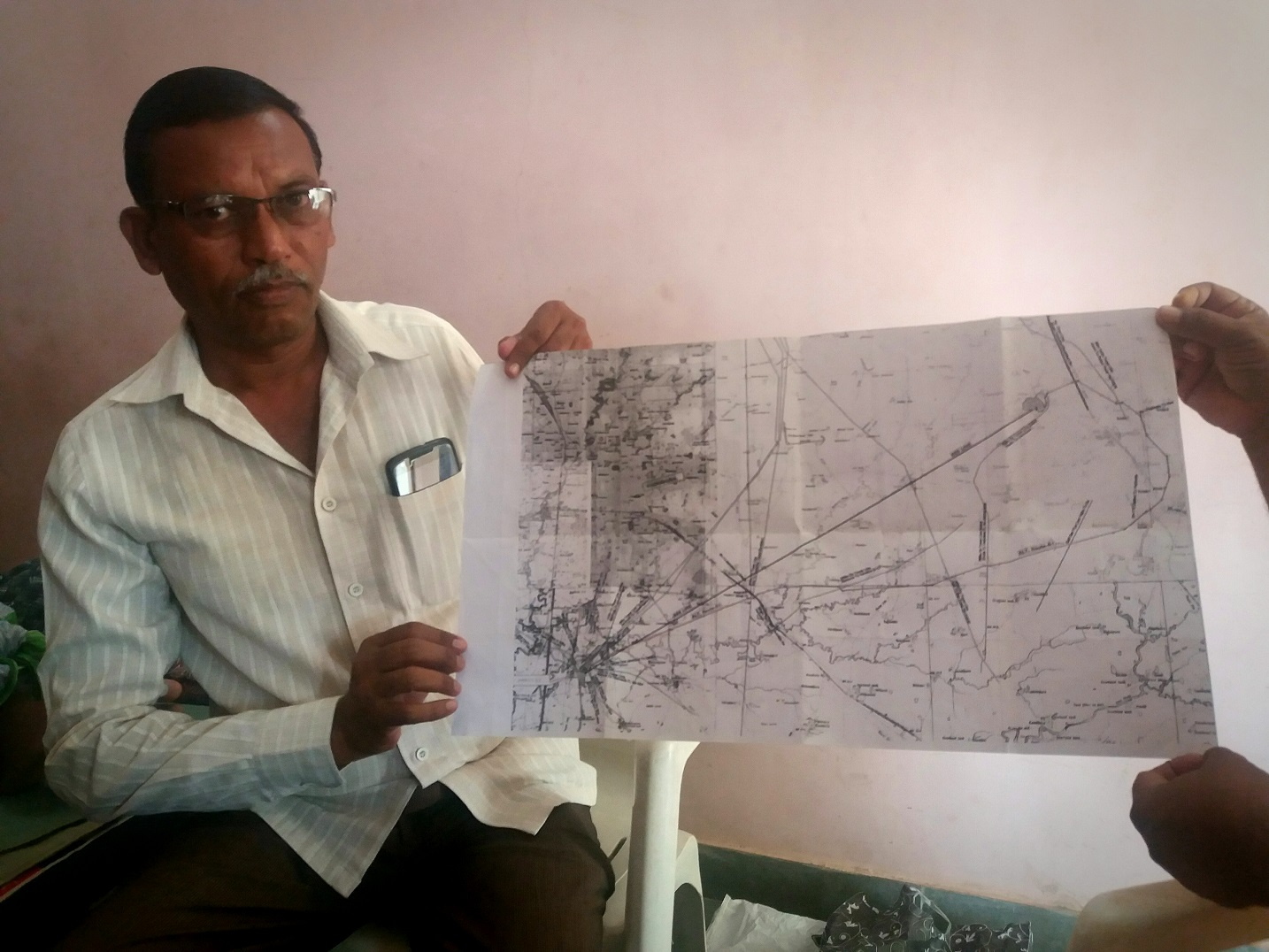 Ashok Patel displays a map of the GETCO power line route running through his farmland.