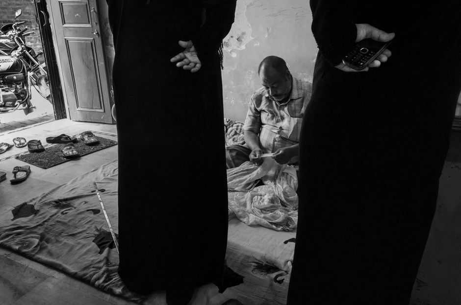 Two women observe Bobby, owner of the Sa-datganj workshop, as he inspects a Mukaish fabric. Photo credit: Taha Ahmad