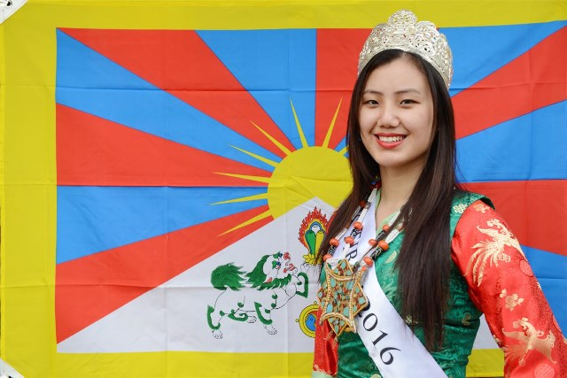 Miss Tibet 2016 Tenzing Sangnyi posing before the Tibetan flag.