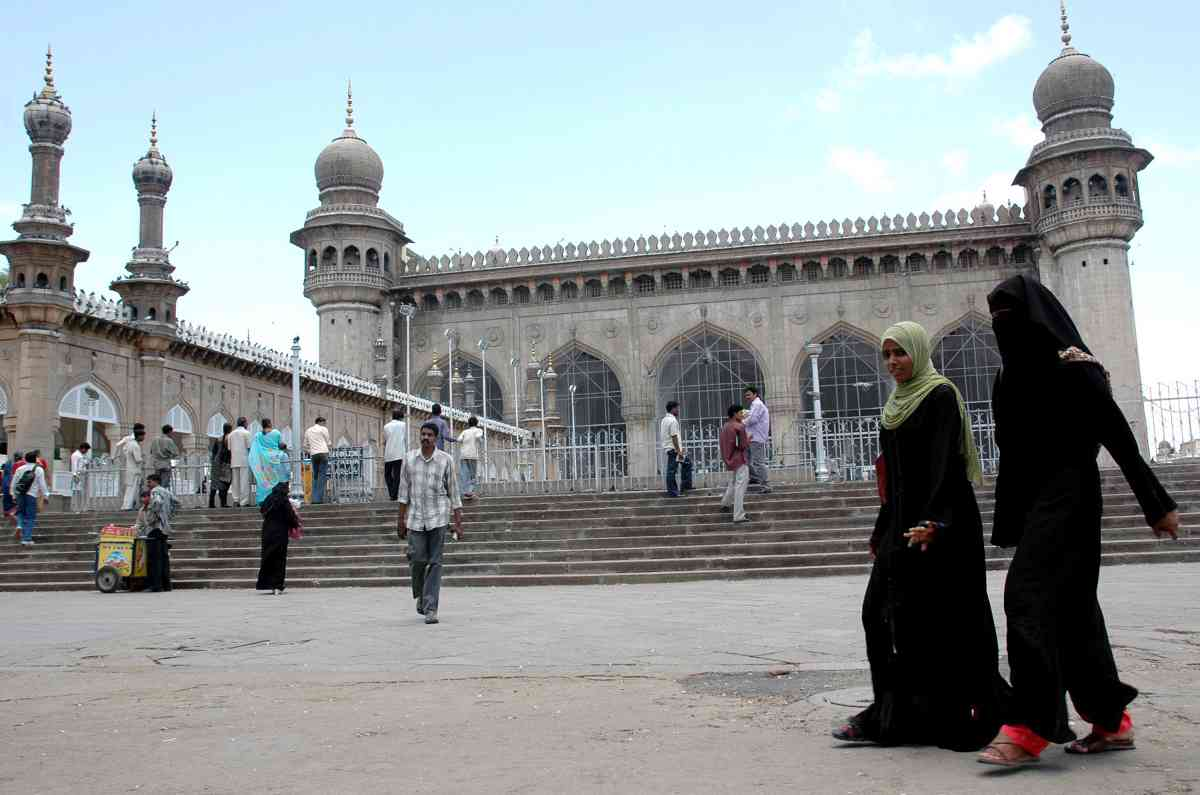 Women walk past the historic Mecca Masjid in the old city of Hyderabad in July 2007. (Photo credit: Noah Seelam/AFP).