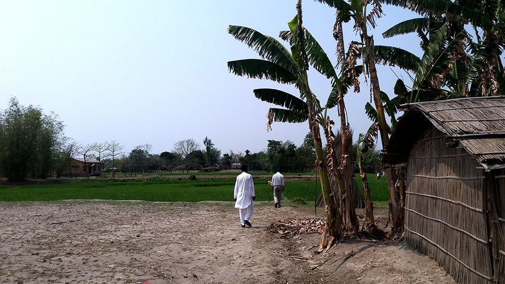 Workers of the All India United Democratic Front walk across a field in Fulkakata.