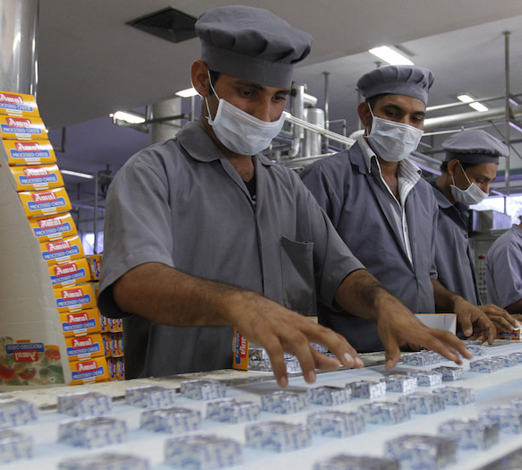 Workers pack processed cheese cubes at an Amul satellite dairy in Khatraj village. Photo credit: Reuters