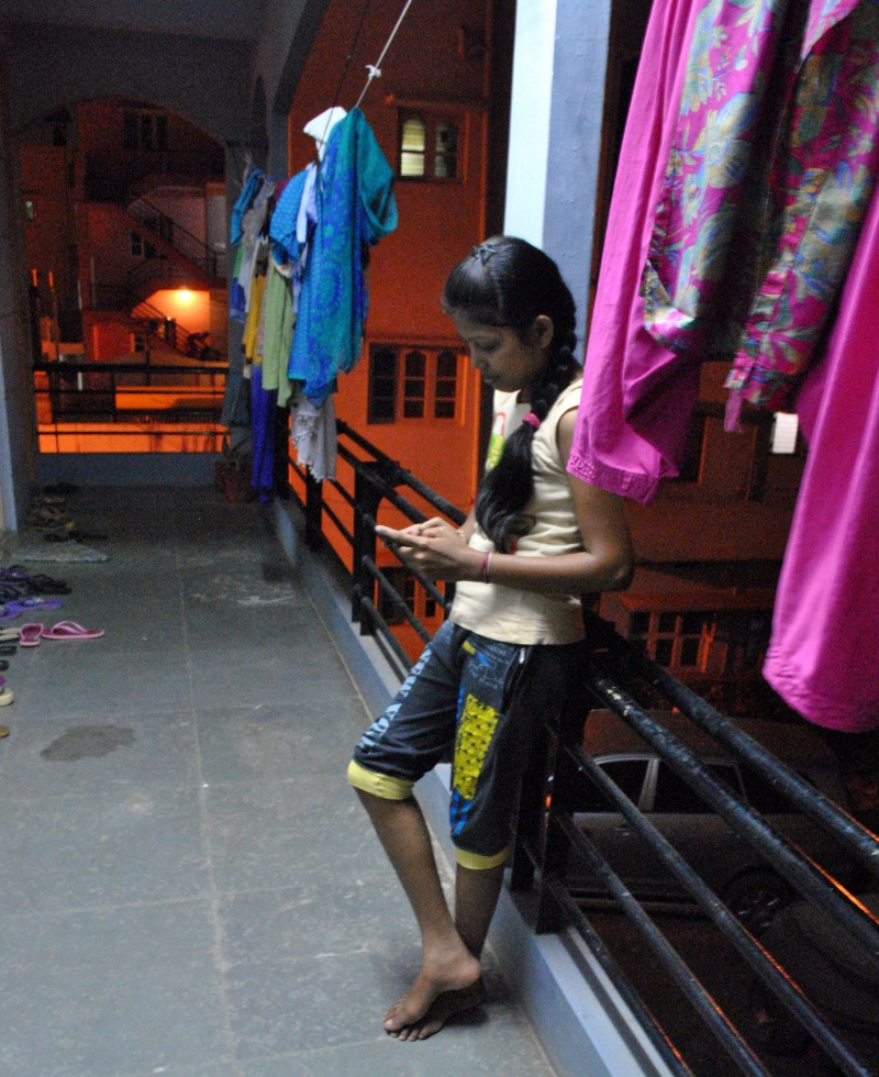 After dinner, a young woman at a garment workers hostel in Bengaluru takes a moment to text her sister in Odisha on WhatsApp. Photo credit: Rohini Mohan.