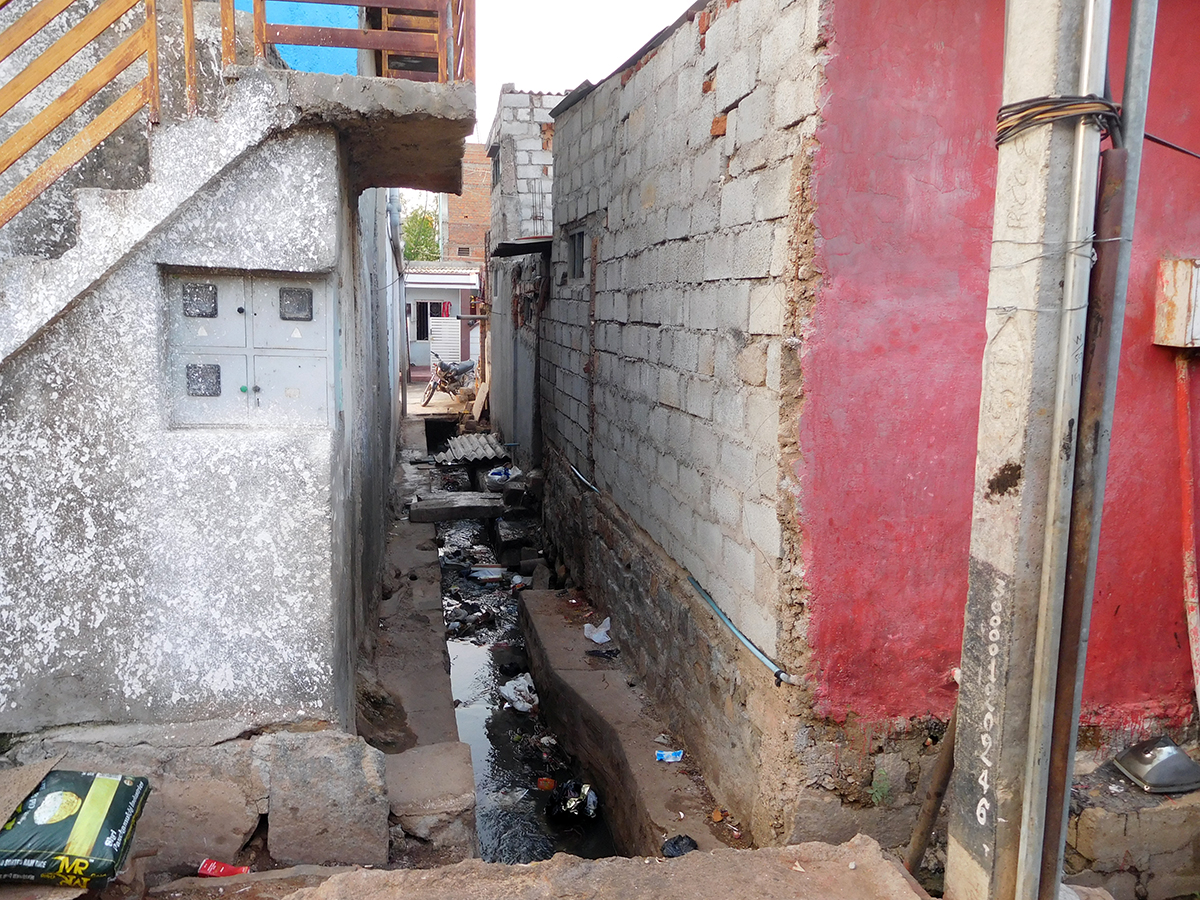 Homes in Mysuru's Ghousia Colony abut open drains and piles of garbage.