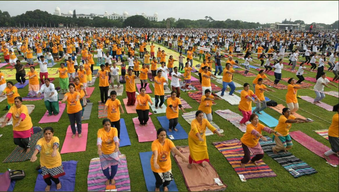 "Around 60,000 people gathered to practice yoga at the Race Course Grounds in Mysuru – ""probably the largest gathering in the world today"", according to the government. (PIB Karnataka/Twitter)"