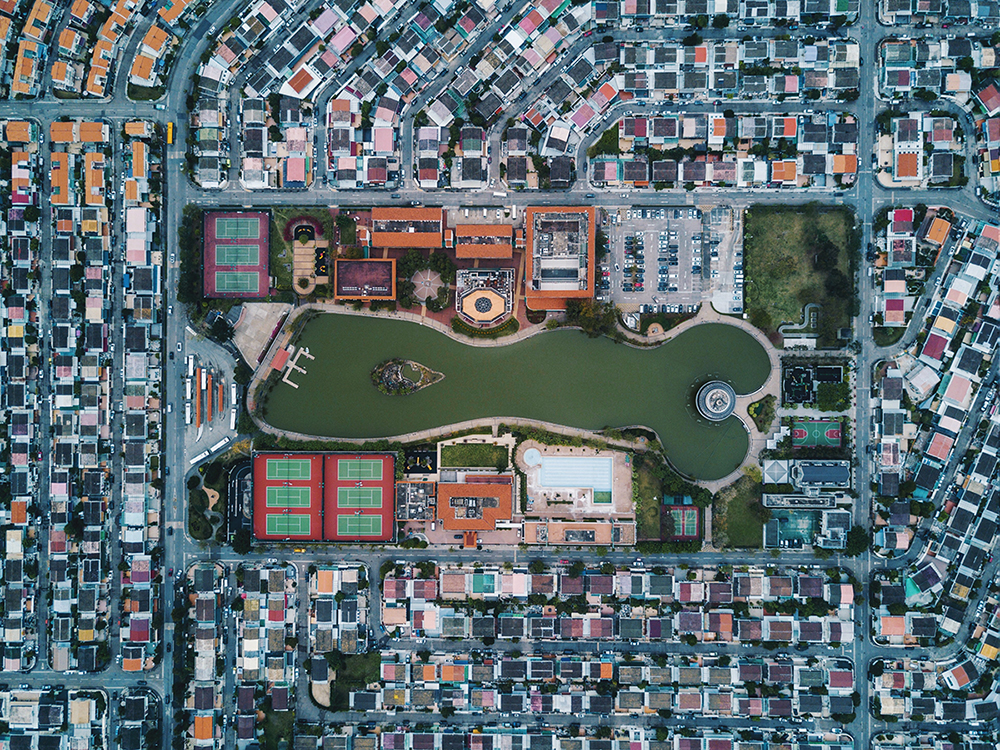 'Playful hidden messages', from the series 'We Live in a Symmetrical World' by Varun Thota. A town in the outskirts of Hong Kong designed to resemble North American suburbs. A large lake at its centre has an interesting shape, deliberate or otherwise, which can only be gleaned from above. © Varun Thota, India, Shortlist, Professional, Landscape (Professional competition), 2018 Sony World Photography Awards.