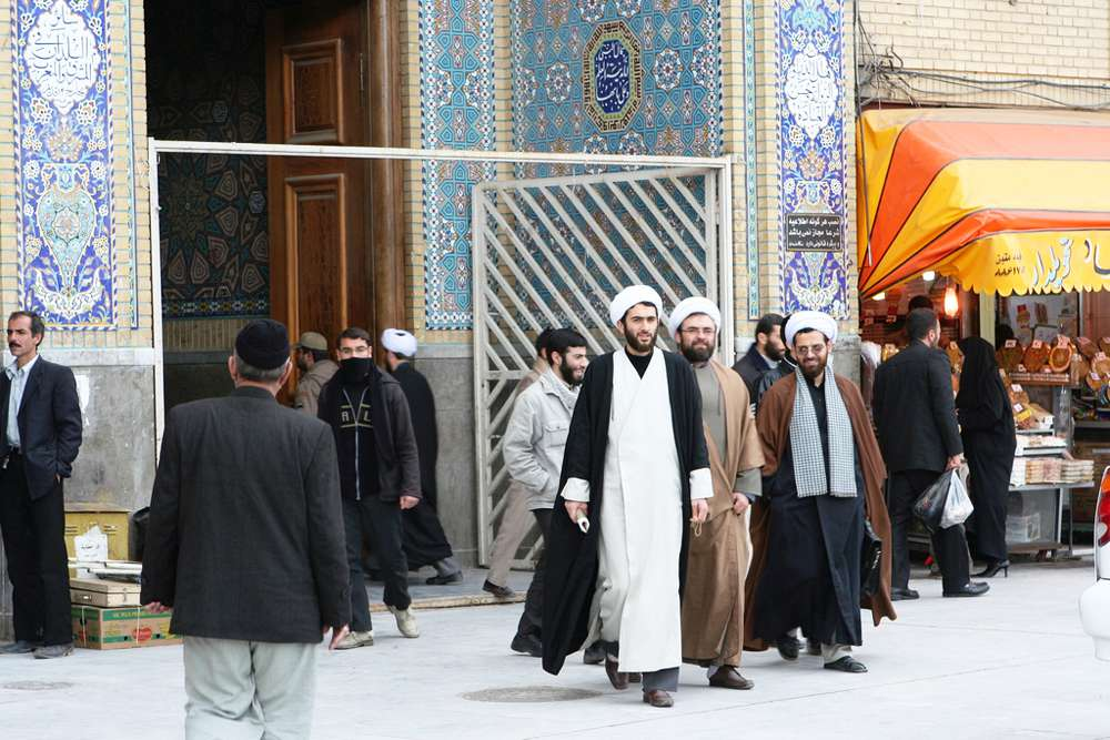 Islamic students exit the shrine of Masumeh Qom. Qom is one of the most important Shia pilgrimage sites in Iran. Qom has also has a centre for theological studies.