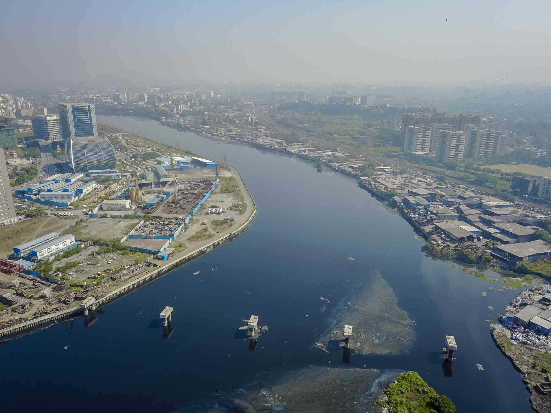 The Mithi River divides the buildings in Bandra Kurla Complex and the slum cluster to the right. Pillars have been laid for the BKC-Chunabhatti elevated road, which will connect the Eastern Express Highway to the busy office complex.