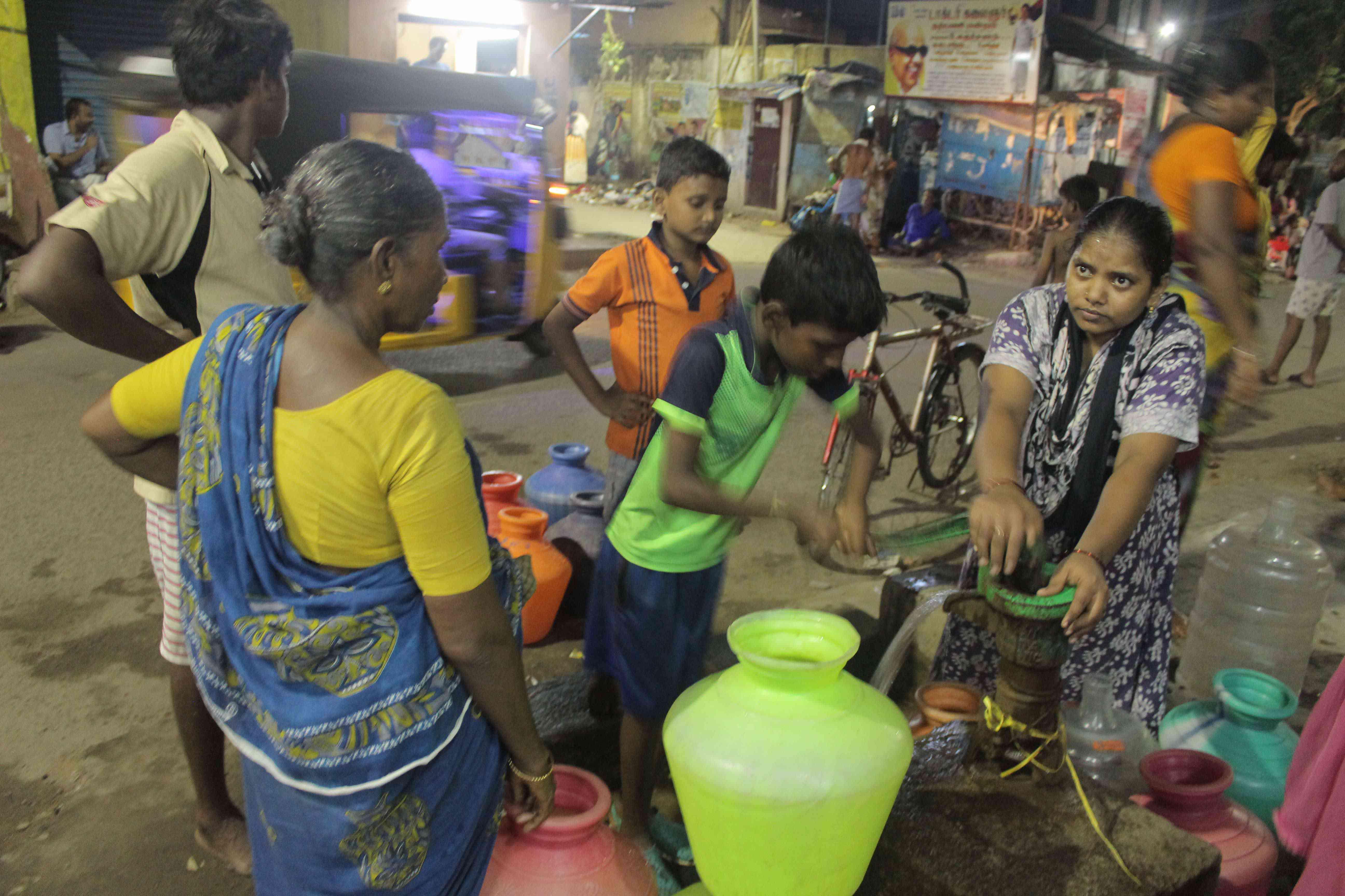 T Nagamma, extreme right, fills water from a hand pump in Anjaneya Nagar, Chennai. Photo credit: S Senthalir