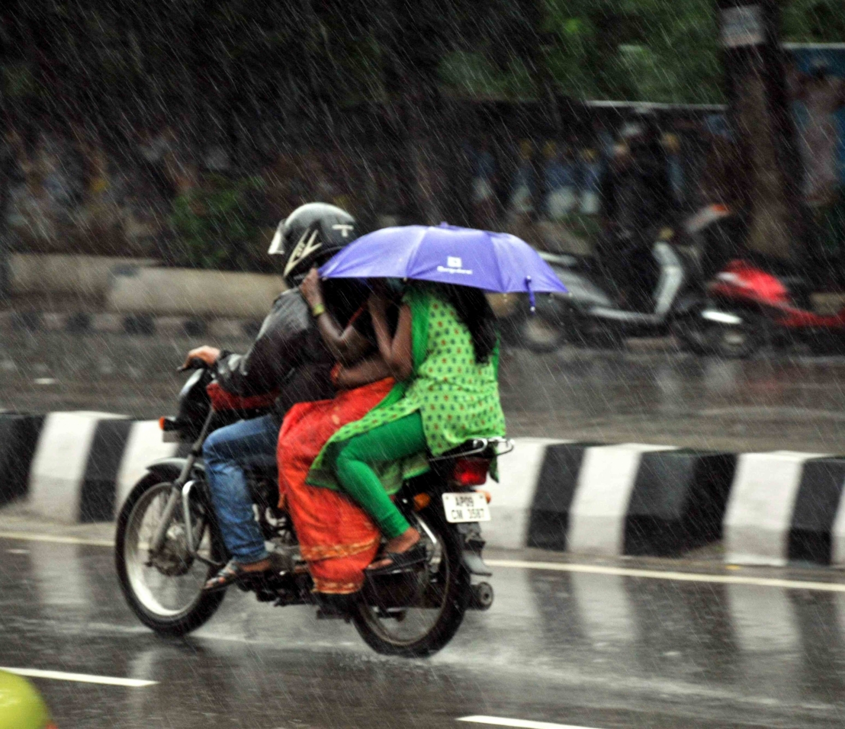 Riders on a motorcycle make a futile attempt at protecting themselves from the rain in Hyderabad. (Credit: IANS)