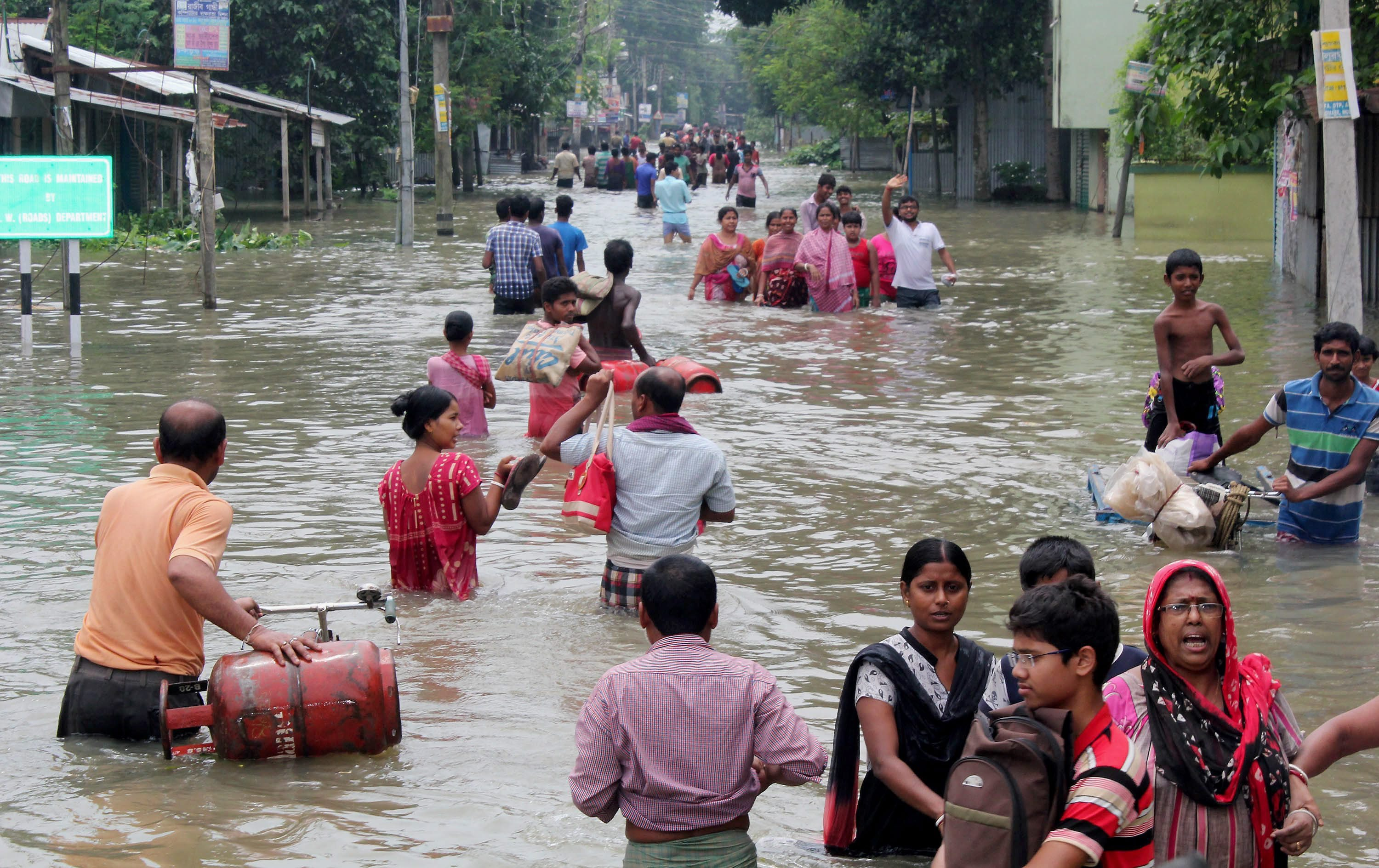 People wade through a flooded road in Bularghat in West Bengal's South Dinajpur district. (Credit: PTI)