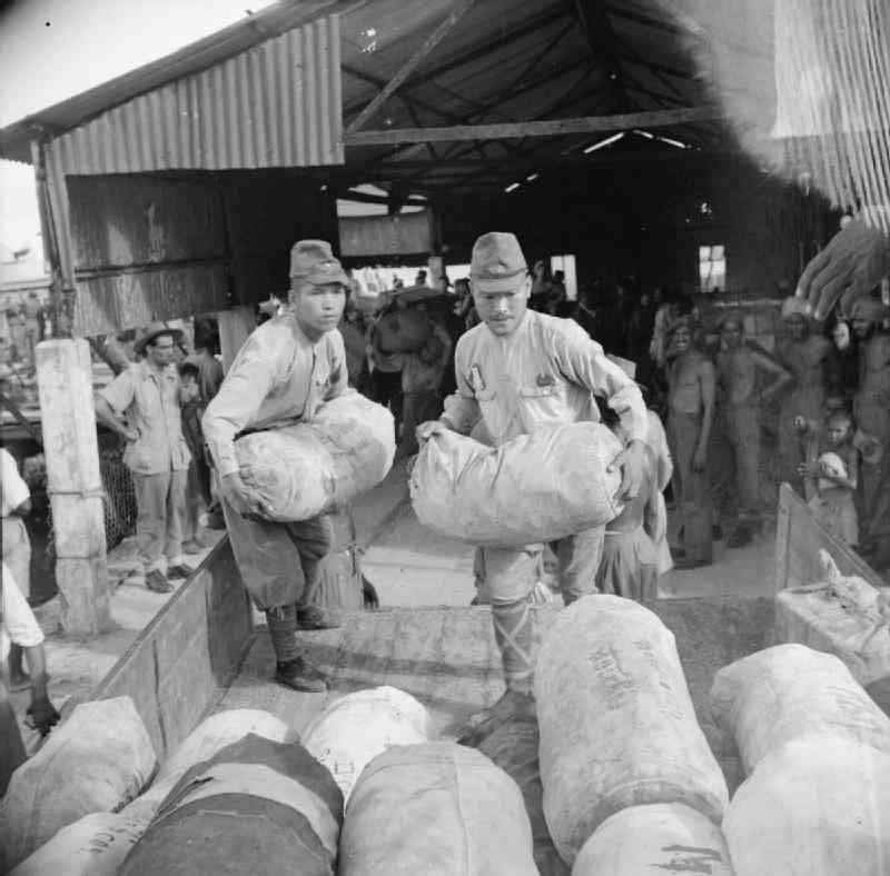 Japanese soldiers unload stores for the Allied occupation forces at Port Blair in the Andaman Islands.