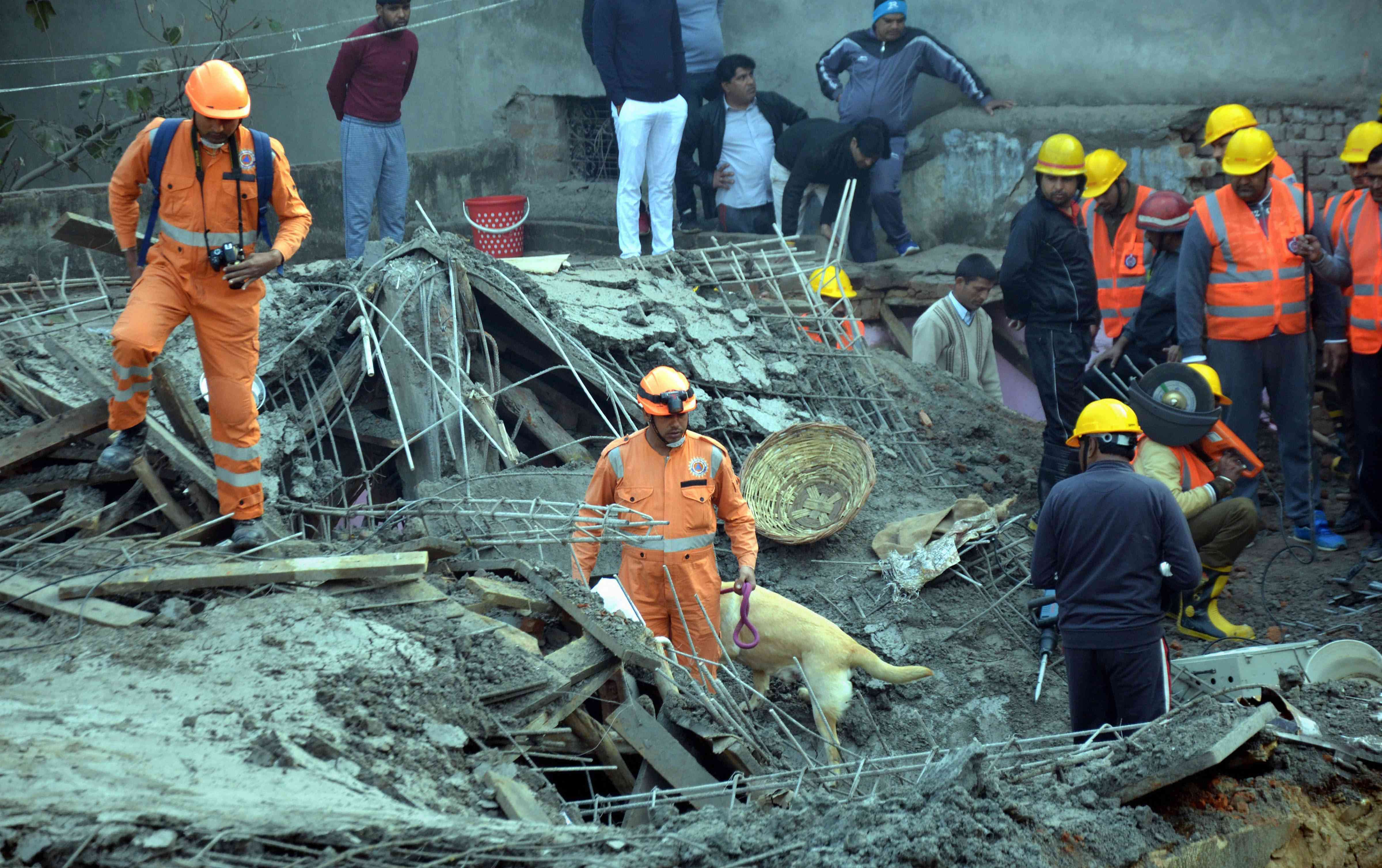 Rescue workers at the site of building collapse in Gurugram on Thursday.