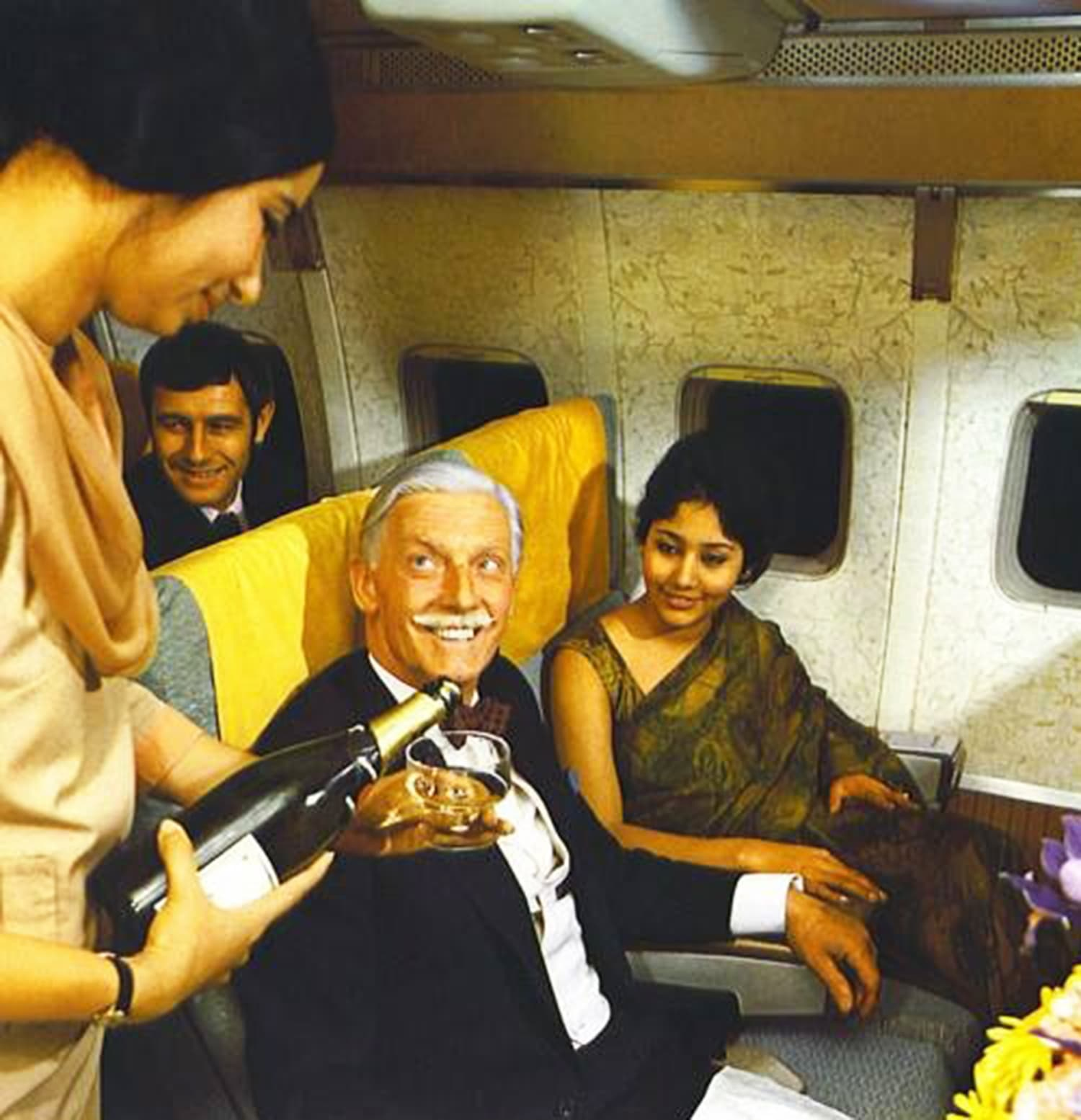 1967: An air-hostess of Pakistan International Airlines pours Champagne for a business-class passenger at Karachi Airport.