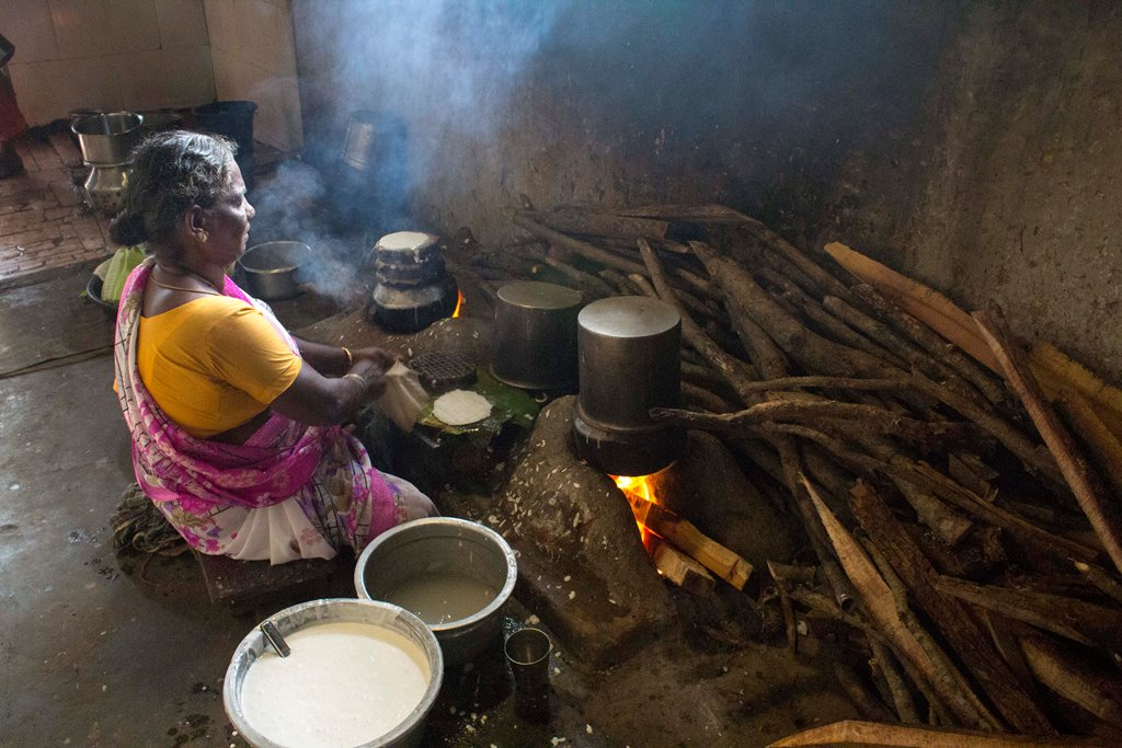Devi makes idlis on a wood fire. Photo credit: Meenakshi Soman