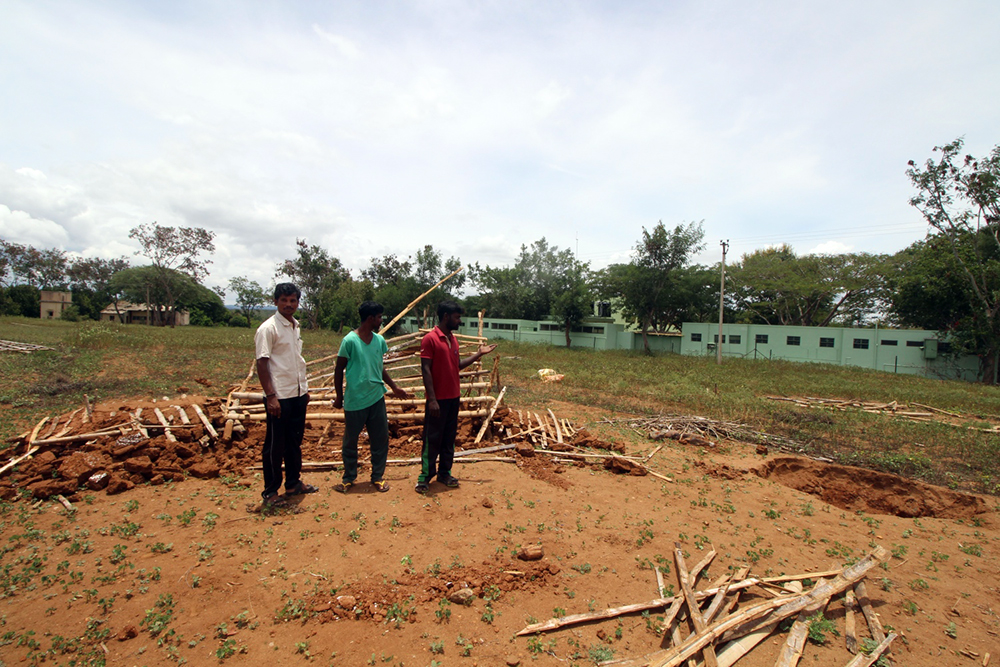 Residents at the eviction site. The wall of the GRG Memorial Tribal School is right alongside it. (Photo credit: Sibi Arasu).