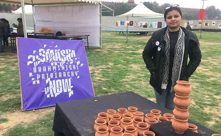 Smita Urmila Ragmane stands next to her installation representing the caste hierarchy. Photo credit: Vijayta Lalwani