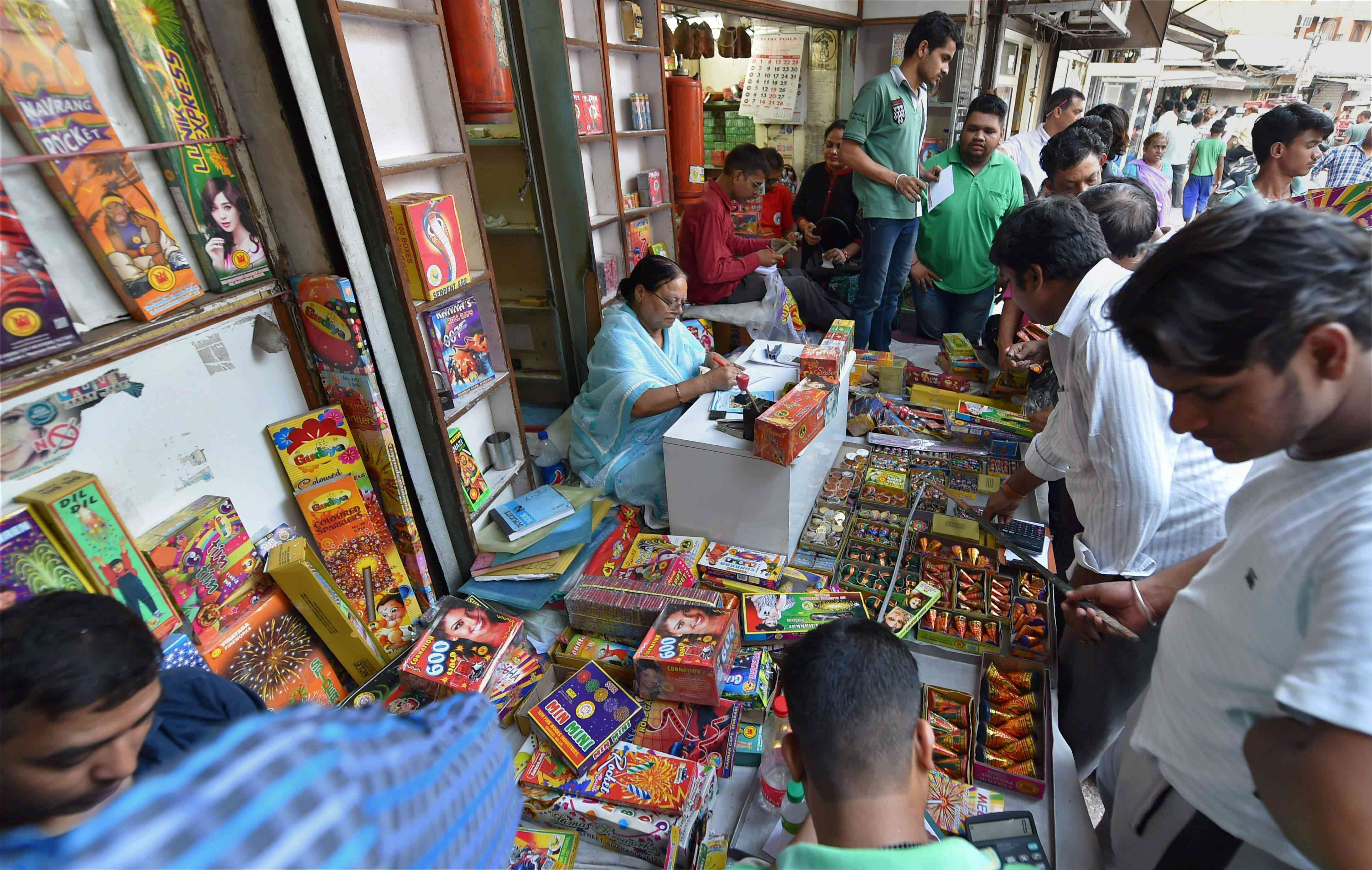 People buy firecrackers near Jama Masjid in old Delhi on Monday. (Photo credit: PTI).