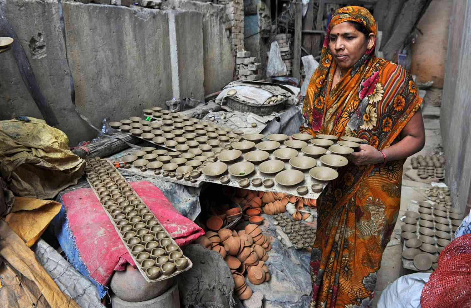 A potter in New Delhi prepares earthen lamps ahead of Diwali in October 2012. (Photo credit: AFP/Sajjad Hussain).