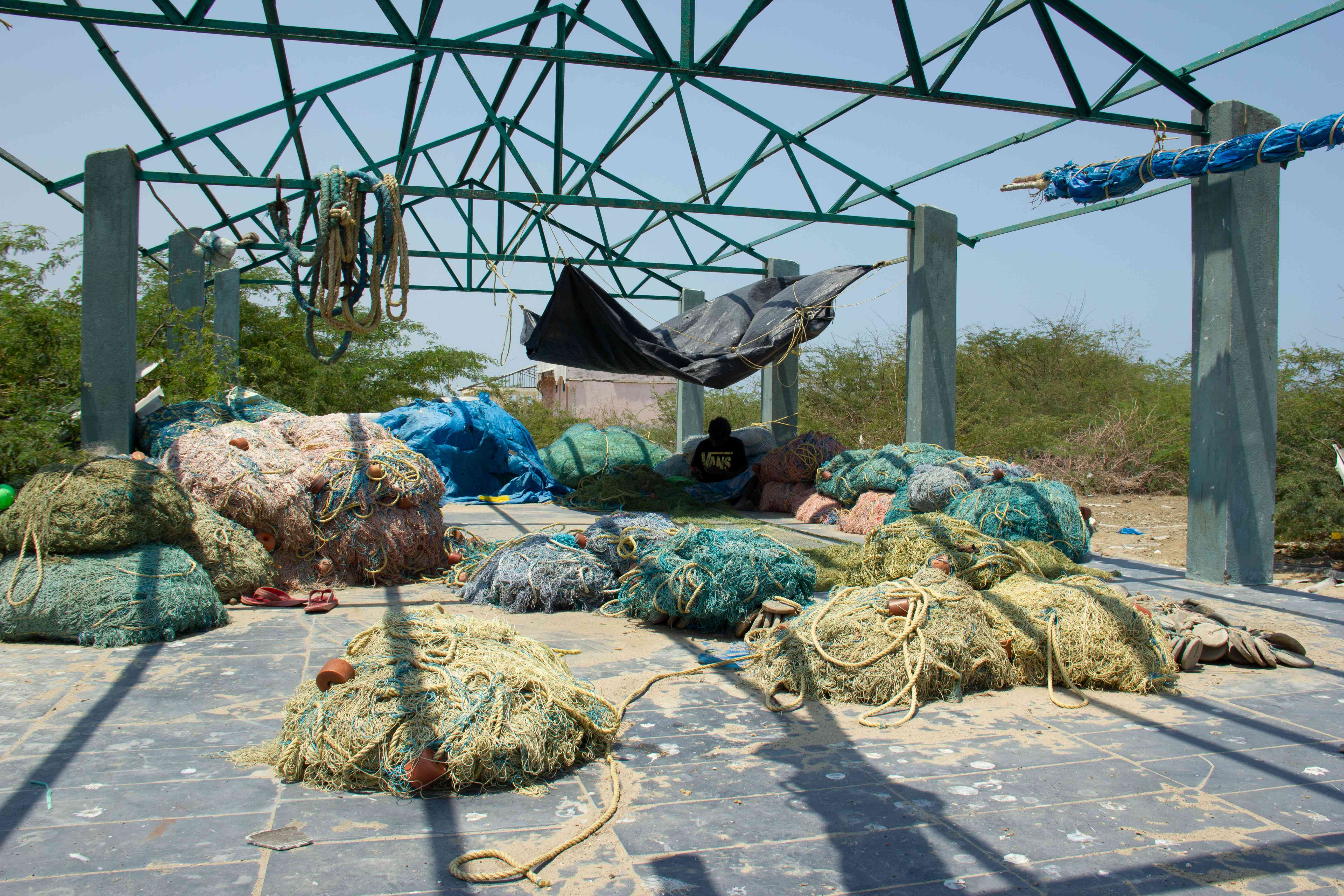 A fisherman sews fishing net in a shed that was damaged during cyclone Gaja. Photo Credit: M Palanikumar|Pepcollective